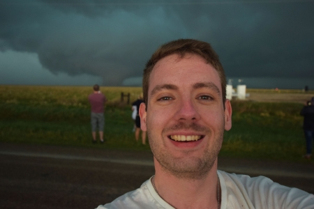 Jason looking happy with a tornado in the background