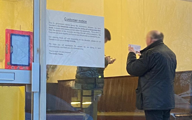a man ordering a takeaway through the window of the restaurant due to coronavirus